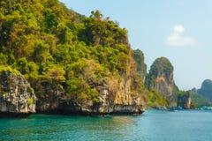 Большой зеленый цвет трясет остров на голубом тропическом море Стоковое Изображение RF