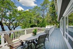 Большой длинний экстерьер дома балкона с таблицей и стулами, взглядом озера. Стоковое фото RF
