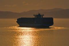 Большой контейнеровоз приходя над морем на заходе солнца Залив Nakhodka Восточное море (Японии) 19 04 2014 Стоковое Изображение RF
