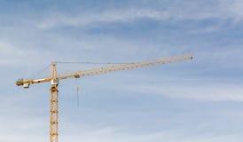 Большой кран конструкции и здание против предпосылки неба Стоковые Фотографии RF