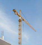 Большой кран конструкции и здание против предпосылки неба Стоковое Изображение