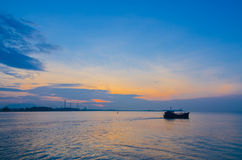 Большой нефтяной танкер и малая рыбацкая лодка Стоковые Изображения