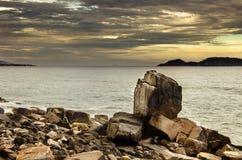 Большой остроконечный камень среди скалистых образований морем Стоковые Фото