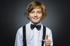 Большой палец руки выставки мальчика портрета крупного плана успешный счастливый вверх изолировал серую предпосылку положительная Стоковое Фото