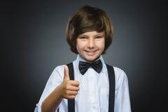 Большой палец руки выставки мальчика портрета крупного плана успешный счастливый вверх изолировал серую предпосылку положительная Стоковые Фото