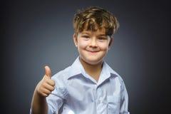 Большой палец руки выставки мальчика портрета крупного плана успешный счастливый вверх изолировал серую предпосылку положительная Стоковые Изображения