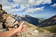 Большой палец руки выставки человека вверх в горах стоковая фотография rf