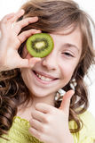 Большой палец руки девушки вверх для витаминов зеленого цвета кивиа Стоковые Изображения