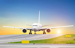 Большой самолет на ездя на такси заходе солнца на авиапорте, небо солнце и след управления рулем Стоковое Фото