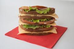 Большой сандвич с беконом и сыром и свежими овощами на красной бумажной салфетке Стоковое Изображение