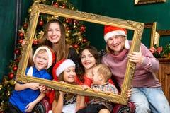 Большой усмехаясь дом семьи в шляпах хелпера santa Стоковая Фотография