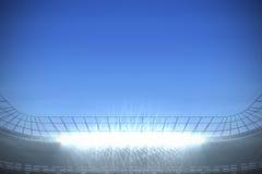 Большой футбольный стадион с фарами под яркой синью Стоковое Изображение RF