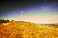 Большой христианский крест стоя na górze холма Radobyl в зоне CHKO Ceske Stredohori на вечере в чехословакском ландшафте лета стоковое фото