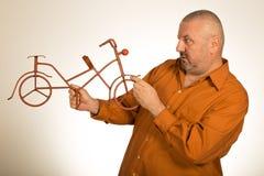 Большой человек держа масштабную модель велосипеда/велосипеда Стоковое Изображение RF