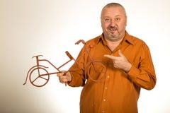 Большой человек держа масштабную модель велосипеда/велосипеда Стоковая Фотография