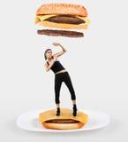 Большой cheeseburger падая на женщину пригонки стоковое изображение rf