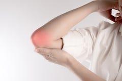 Боль в локте ` s женщины изолированном на белой предпосылке Стоковая Фотография