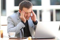 Боль исполнительной власти страдая головная в кофейне Стоковые Изображения RF