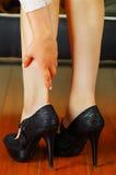 Боль ног ботинка высоких пяток Женщина приняла ее ботинки от усталости в ногах расположите положение Стоковая Фотография RF