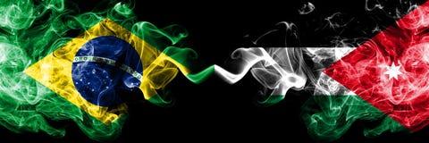 Бразилия против Джордан, йорданськие флаги дыма установила сторону - - сторона Толстые покрашенные шелковистые флаги дыма бразиль стоковая фотография rf