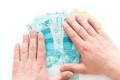 Бразильские деньги, reais, высокие деноминации держали в ладони вашей руки Стоковые Изображения RF