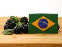 Бразильский флаг на деревянной панели при ежевики изолированные на a стоковые изображения rf