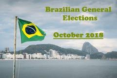 Бразильский флаг на комплекте поляка развевая против Copacabana, Рио-де-Жанейро, Бразилии, с сообщением предстоящих всеобщих выбо стоковая фотография rf
