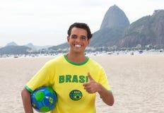 Бразильский вентилятор спорт с шариком на Рио-де-Жанейро показывая большой палец руки вверх Стоковые Фотографии RF