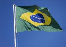 Бразильский флаг на голубом небе Стоковое фото RF