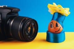 Брайн, положительное яичко в одеждах и шляпе при смычок представляя перед камерой на сине-желтой предпосылке, конец-вверх Стоковая Фотография