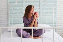 Брайн-с волосами дама в пижамах выпивая ее кофе утра на кровати Стоковая Фотография RF