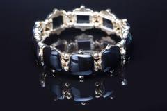 Браслет с черными камнями над чернотой Стоковое Изображение
