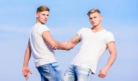 Братья близнецов людей мышечные в белой предпосылке неба рубашек концепция братства Преимущества и недостатки иметь стоковое фото rf