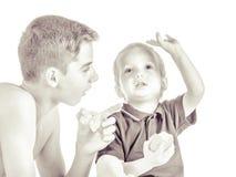 Братья играя и есть яблока Стоковое Изображение