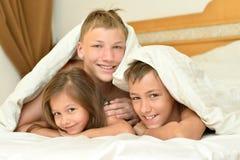 Братья и сестра под одеялом Стоковые Фотографии RF