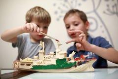 Братья крася деревянную модель военного корабля Стоковое Изображение