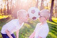 Братья мальчиков играя с шариком на зеленой траве в парке стоковая фотография