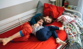 Братья щекоча и смеясь над лежать на кровати стоковое изображение rf
