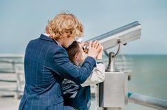 2 брать белокурых волос смотрят совместно в биноклях на море Стоковое Фото