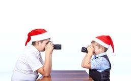 2 брать в крышках Санта Клауса фотографировать одина другого Стоковое Изображение
