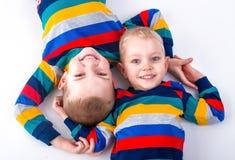 2 брать играют, имеют потеху, делают друзей Дети одетые в таких же одеждах Стоковая Фотография