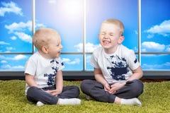 2 брать играют, имеют потеху, делают друзей Дети одетые в таких же одеждах Стоковое Изображение