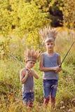 2 брать имеют крону от сухой травы на голове и шпагах в руках Концепция утехи и игры Стоковая Фотография RF