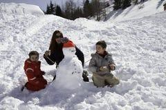 2 брать и мать с снеговиком Стоковая Фотография