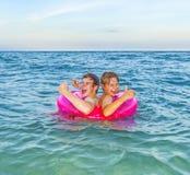 2 брать мальчиков в кольце заплыва имеют потеху в океане Стоковые Изображения