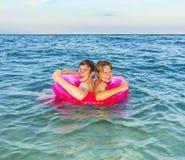 2 брать мальчиков в кольце заплыва имеют потеху в океане Стоковое Изображение RF