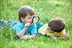 2 брать мальчиков с лупой outdoors Стоковое Изображение RF