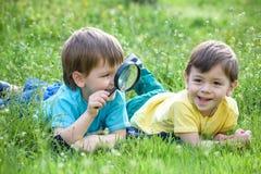 2 брать мальчиков с лупой outdoors Стоковые Изображения