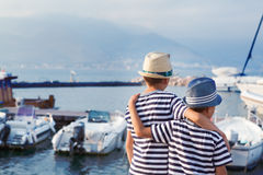 2 брать обнимают и смотрят корабли, яхту на море Стоковые Изображения RF