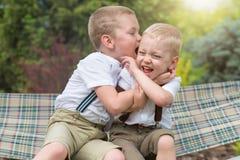 2 брать отдыхают, говорящ секреты в его ухе Езда мальчиков в гамаке Стоковое фото RF